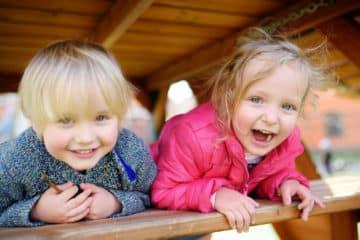 Zwei lachende Kinder liegen auf einer Bank