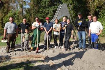 EIne Gruppe von 10 Personen mit Werkzeugen in der Hand steht vor einer Rutsche