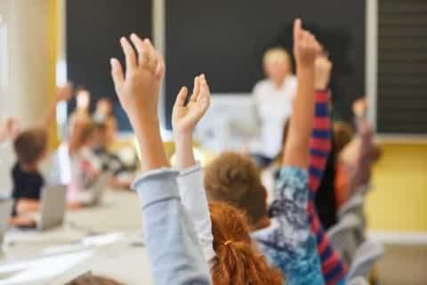 Schüler im Unterricht der Grundschule antworten auf eine Frage und melden sich