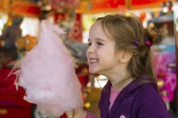 Ein kleines Mädchen auf einem Kirtag mit Zuckerwatte. Spaß und Freude am Jahrmarkt