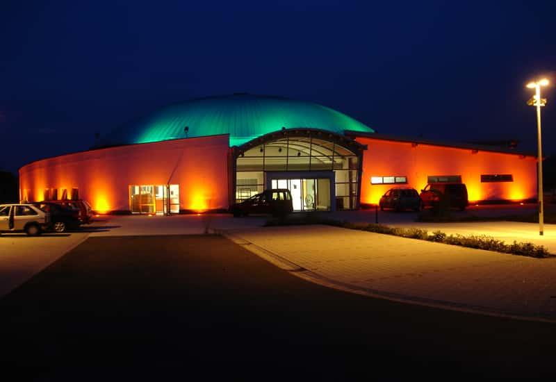 Außenansicht der Kulturhalle Ochtendung bei Nacht mit eindrucksvoller Beleuchtung