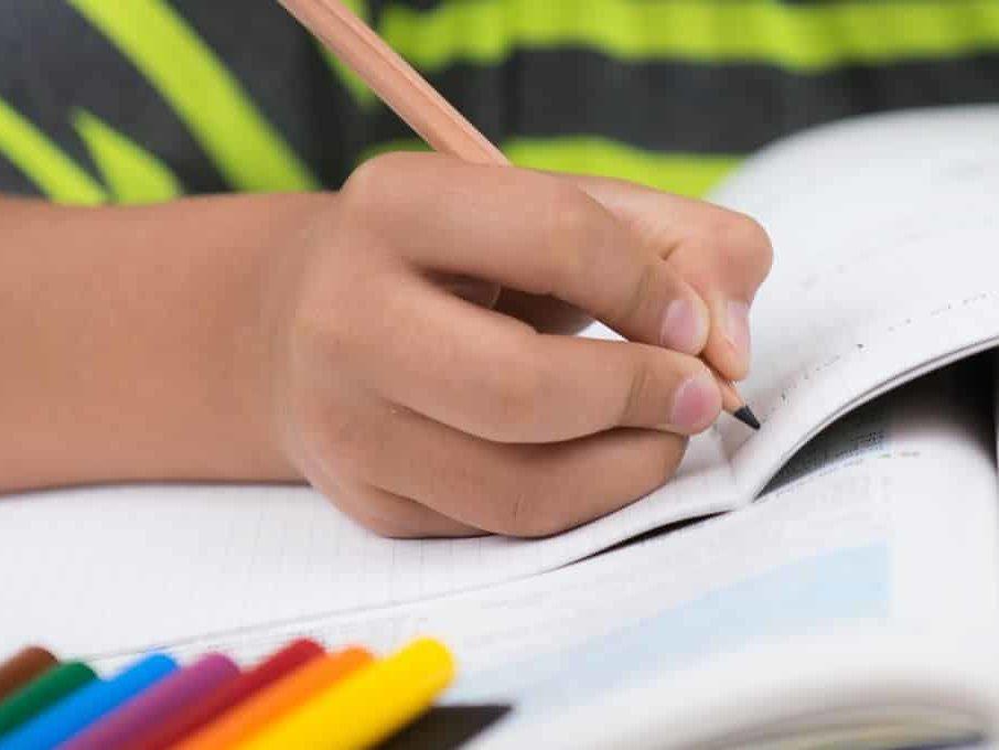Ein Kind schreibt in ein Schulheft