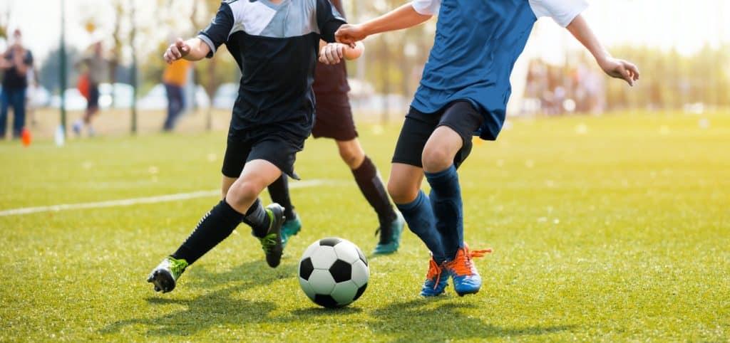 Zwei Fußballspieler im Anschnitt auf grünem Rasen