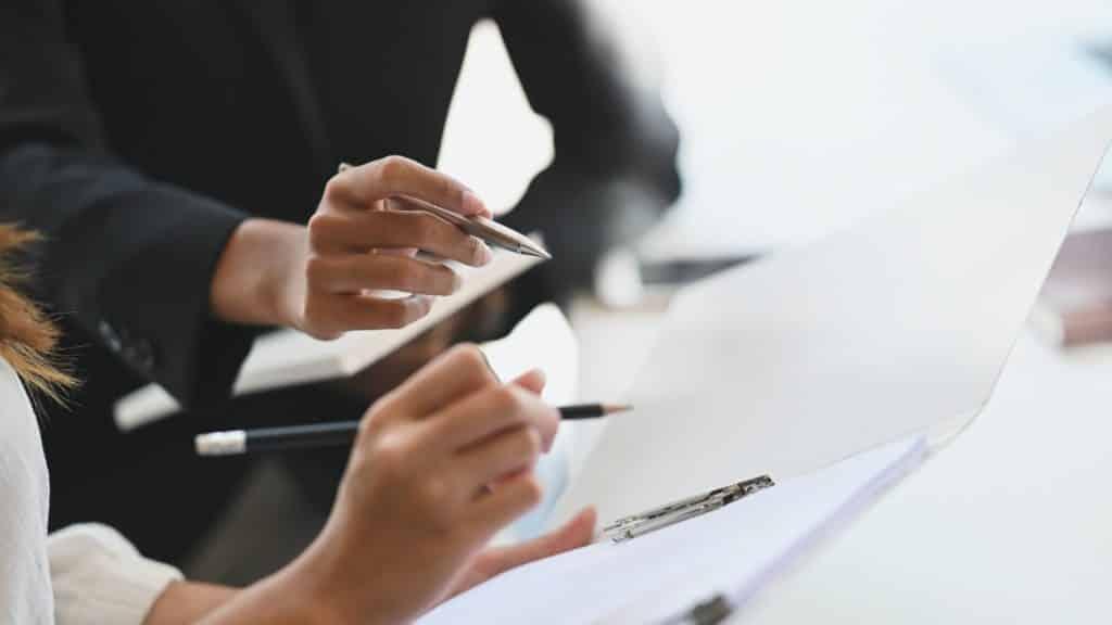 Zwei Personen zeigen mit Stiften auf geöffnete Arbeitsmappen