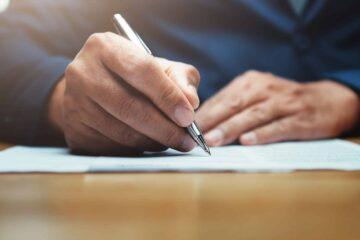 EIn Mann schreibt auf einem Dokument